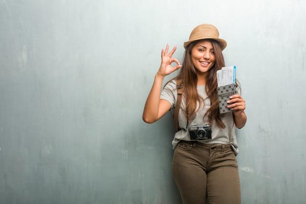 Portret młoda podróżnik łacińska kobieta przeciw ściennemu rozochoconemu i ufnemu robi ok gestowi