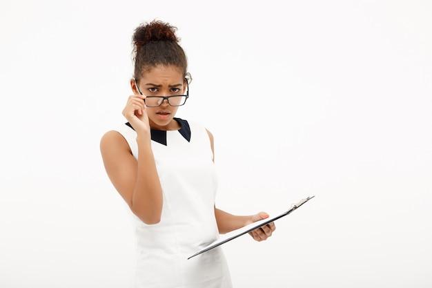 Portret młoda pomyślna afrykańska biznesowa dama na bielu