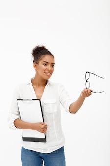 Portret młoda pomyślna afrykańska biznesowa dama nad biel ścianą