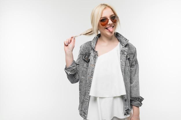 Portret młoda powabna radosna blondynka w drelichowej kurtce pozuje i gestykuluje w round szkłach na białym pracownianym tle