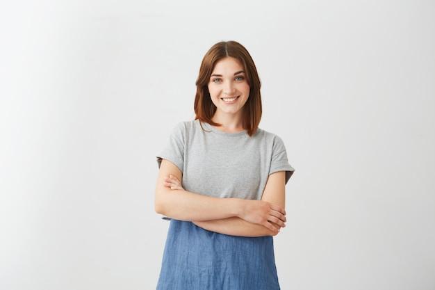 Portret młoda rozochocona piękna dziewczyna ono uśmiecha się z krzyżować rękami.