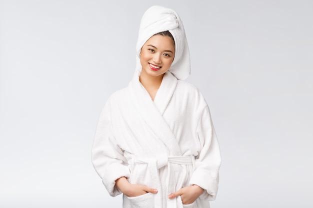 Portret młoda szczęśliwa azjatykcia dama w bathrobe. odizolowywający w białym tle.
