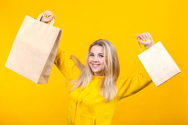 Portret młoda szczęśliwa caucasian blondynki kobieta z papierowymi eco torbami w żółtym sportowym kostiumu, odizolowywający na żółtym tle