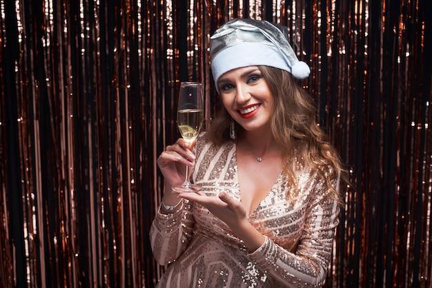 Portret młoda szczęśliwa kobieta w srebnym santa kapeluszu z szampańskim szkłem w rękach.