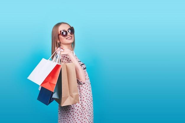 Portret młoda szczęśliwa uśmiechnięta kobieta z torba na zakupy na błękicie