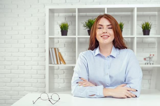 Portret młoda szczęśliwa uśmiechnięta rozochocona biznesowa kobieta przy biurem