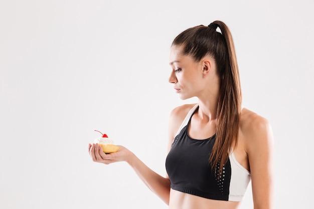 Portret młoda szczupła sportsmenka trzyma babeczkę