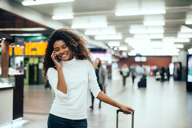 Portret młoda turystyczna kobieta opowiada na telefonie przy lotniskiem.