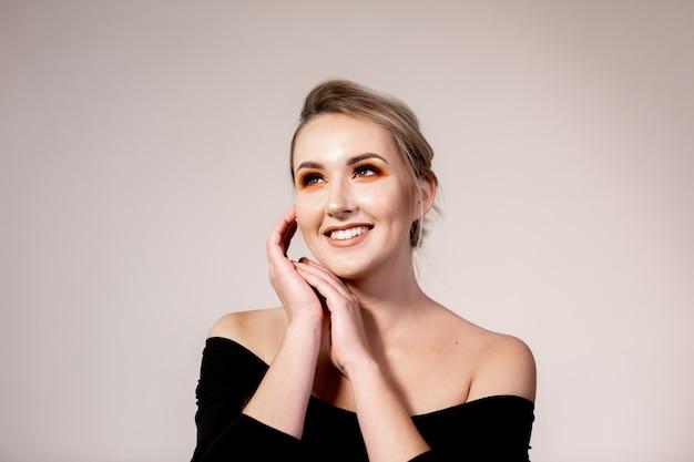 Portret młoda uśmiechnięta blondynki kobieta z fachowym makeup.