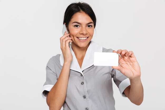 Portret młoda uśmiechnięta brunetki kobieta opowiada na telefonie komórkowym w mundurze podczas gdy pokazywać pustą znak kartę