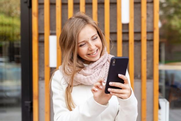 Portret młoda uśmiechnięta kobieta w białym żakiecie dotyka smartphone w szaliku