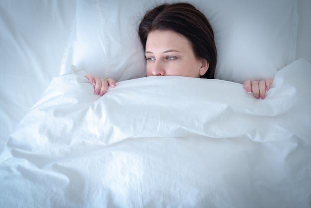 Portret młoda wzburzona kobieta w łóżku, błękitny brzmienie