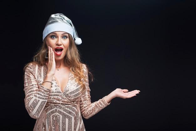 Portret młoda zdziwiona kobieta w santa kapeluszowym mieniu coś na jej ręce.