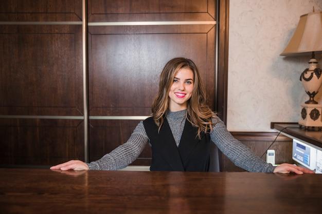 Portret młoda życzliwa recepcjonista stoi przy jej biurkiem