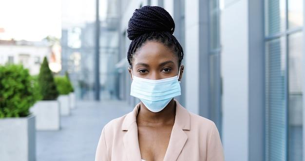 Portret młodego african american piękna kobieta w różowej kurtce zdejmując maskę medyczną i uśmiechając się do kamery na zewnątrz. atrakcyjna wesoła bizneswoman na ulicy w pobliżu centrum biznesowego w kwarantannie.