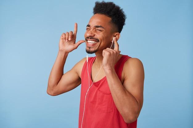 Portret młodego afroamerykanina czuje się świetnie i bardzo szczęśliwy, ma zamknięte oczy, lubi swoją ulubioną piosenkę, śpiewa i tańczy na trybunach.