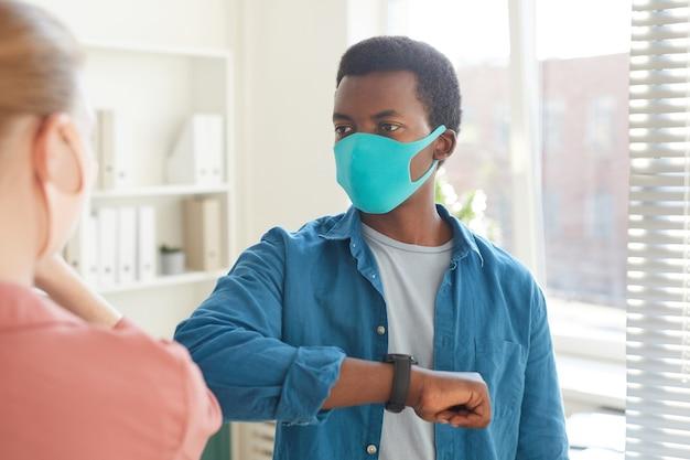 Portret młodego afroamerykanina w masce, obijającego się łokciami z kolegą jako bezdotykowe powitanie podczas pracy w biurze po pandemii