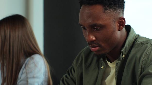 Portret młodego afroamerykańskiego biznesmena patrzącego na ekran komputera typu tablet i omawiającego nowy projekt startowy w nowoczesnym biurze