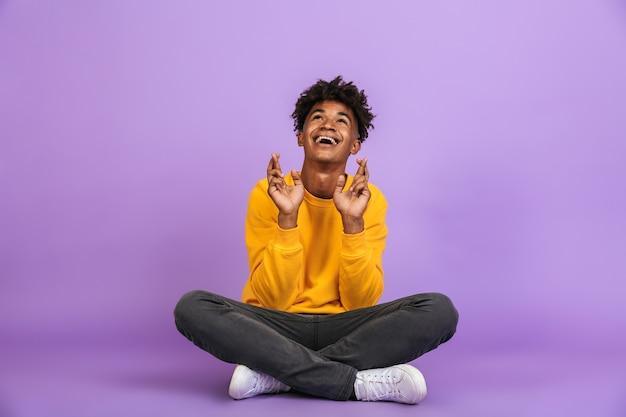 Portret młodego afroamerykańskiego chłopca uśmiechającego się i trzymającego skrzyżowane palce, siedzącego w pozie lotosu, odizolowanego na fioletowym tle