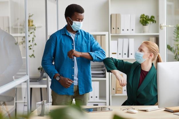 Portret młodego afroamerykańskiego mężczyzny noszącego maskę uderzającego łokciami z koleżanką jako bezdotykowe powitanie w biurze po pandemii