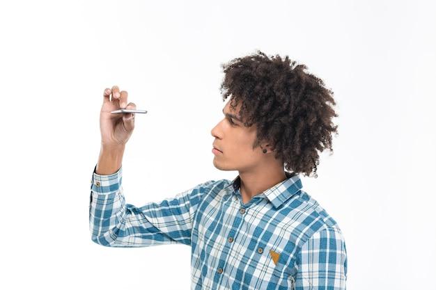 Portret młodego afroamerykańskiego mężczyzny patrzącego na smukły smartfon wyizolowany na białej ścianie