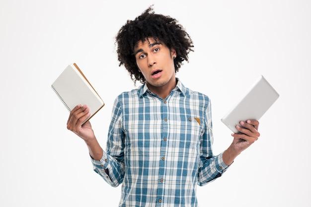 Portret młodego afroamerykańskiego mężczyzny wybierającego między papierową książką a komputerem typu tablet na białej ścianie