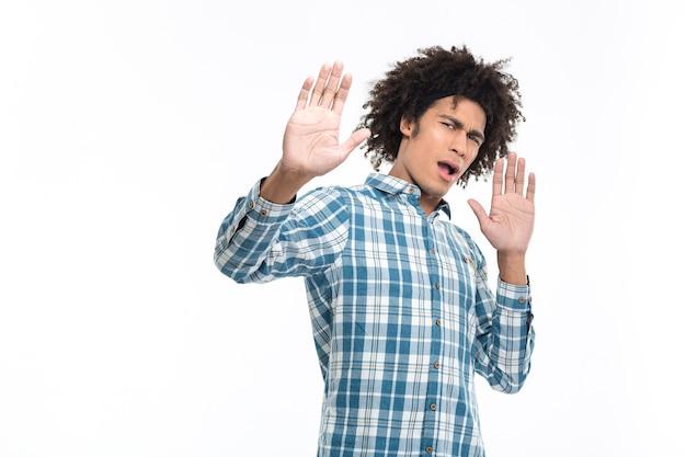 Portret młodego afroamerykańskiego mężczyzny z emocją obrzydzenia stojącego na białym tle na białej ścianie