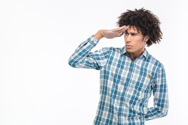 Portret młodego afroamerykańskiego mężczyzny z kręconymi włosami, patrząc w dal na białym tle na białej ścianie
