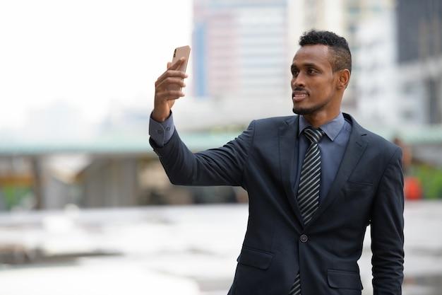 Portret młodego afrykańskiego biznesmena na ulicach miasta na zewnątrz