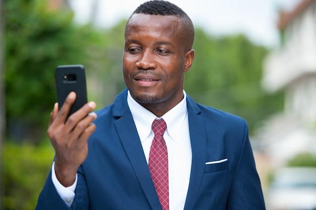 Portret młodego afrykańskiego biznesmena na ulicach na zewnątrz