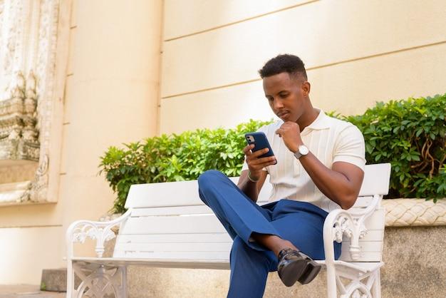 Portret młodego afrykańskiego biznesmena noszącego zwykłe ubrania i korzystającego z telefonu komórkowego podczas siedzenia