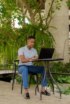 Portret młodego afrykańskiego biznesmena noszącego zwykłe ubrania i siedzącego w kawiarni podczas korzystania z laptopa i dystansu społecznego
