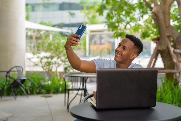 Portret młodego afrykańskiego biznesmena noszącego zwykłe ubrania i siedzącego w kawiarni podczas korzystania z telefonu komórkowego i laptopa oraz biorącego selfie lub wideorozmowy