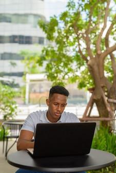 Portret młodego afrykańskiego biznesmena noszącego zwykłe ubrania i siedzącego w kawiarni przy użyciu laptopa