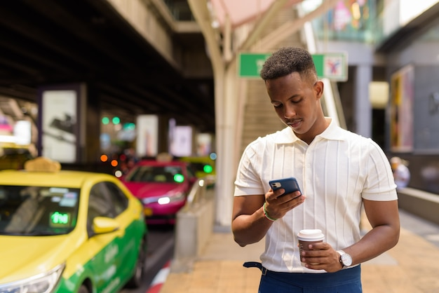 Portret młodego afrykańskiego biznesmena noszącego zwykłe ubrania podczas korzystania z telefonu komórkowego i trzymającego filiżankę kawy na postoju taksówek w mieście