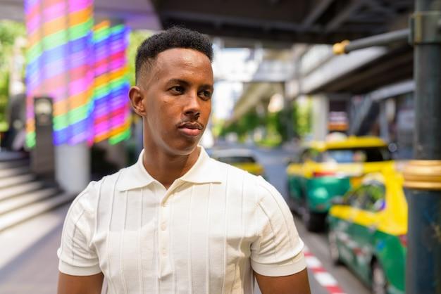 Portret młodego afrykańskiego biznesmena noszącego zwykłe ubrania podczas oczekiwania na taksówkę