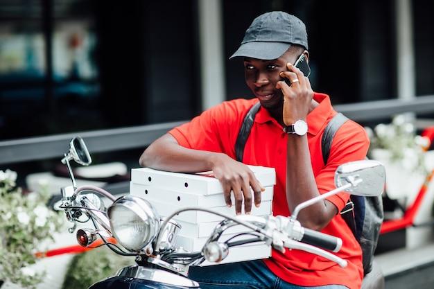 Portret młodego afrykańskiego faceta przyjmuje zamówienie przez telefon w motocyklu trzymając pudła z pizzą i siada na swoim rowerze.