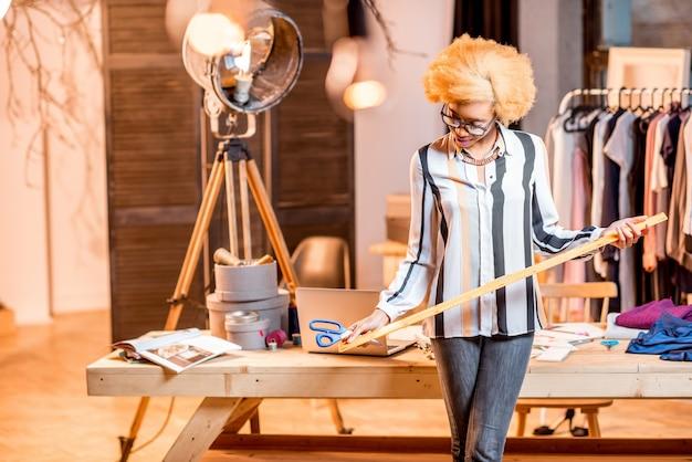 Portret młodego afrykańskiego projektanta mody stojącego z władcą w biurze z różnymi narzędziami krawieckimi i ubraniami