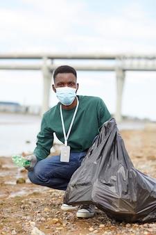 Portret młodego afrykańskiego wolontariusza wkładającego śmieci do torby i patrzącego na aparat podczas pracy w mieście
