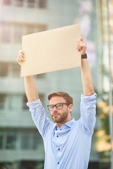 Portret młodego aktywisty mężczyzny w niebieskiej koszuli i okularach, trzymającego pustą tablicę, podczas gdy