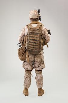 Portret młodego amerykańskiego żołnierza amerykańskiego korpusu piechoty morskiej na szarym tle