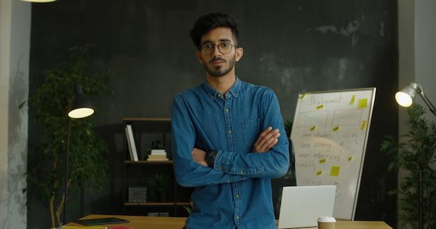 Portret młodego arabskiego przystojnego faceta w niebieskich dżinsach koszula i szkłach siedzi na biurku w biurowym pokoju, krzyżuje ręki i ono uśmiecha się kamera.