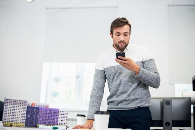Portret młodego architekta rozmawiającego z kimś przez telefon za pomocą trybu głośnomówiącego