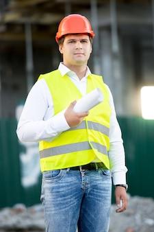 Portret młodego architekta w kasku pozuje z planami przeciw rusztowaniu