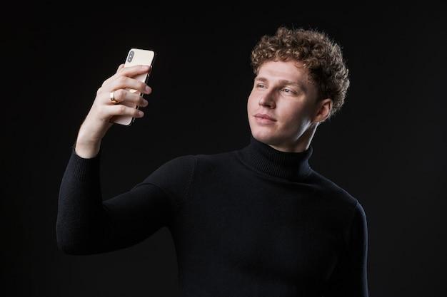 Portret młodego, atrakcyjnego biznesmena z kręconymi włosami stojącego przed czarną ścianą i robiącego selfie