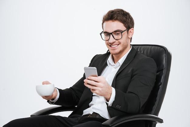 Portret młodego atrakcyjnego biznesmena z telefonem komórkowym i filiżanką kawy na krześle na białym tle na białej ścianie