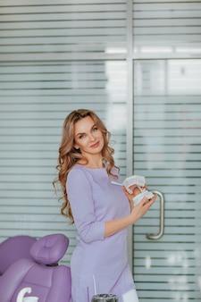 Portret młodego atrakcyjnego lekarza dentysty z długimi kręconymi włosami w fioletowym mundurze medycznym z plastikowymi ustami w gabinecie.