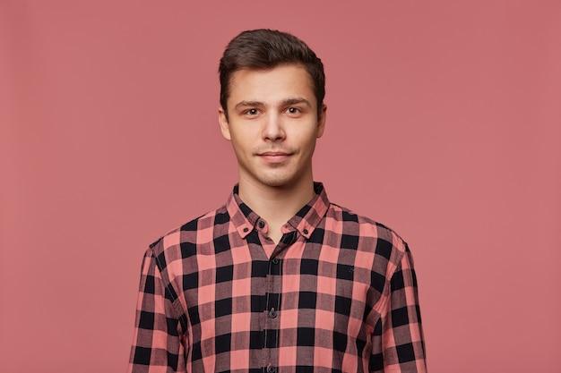 Portret młodego atrakcyjnego mężczyzny w kraciastej koszuli, spokojnie patrzy w kamerę, stoi na różowym tle.