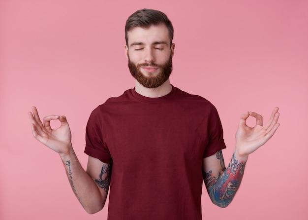 Portret młodego atrakcyjnego mężczyzny z czerwoną brodą w pustej koszulce, wygląda spokojnie i spokojnie, uśmiecha się, stoi na różowym tle z zamkniętymi oczami i pokazuje gest om.