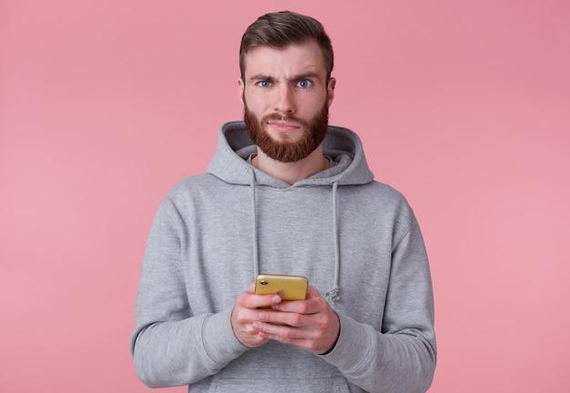 Portret młodego atrakcyjnego mężczyzny z czerwoną brodą w szarej bluzie z kapturem, niezadowolony, trzymając smartfon, patrzy na aparat i stoi na różowym tle.